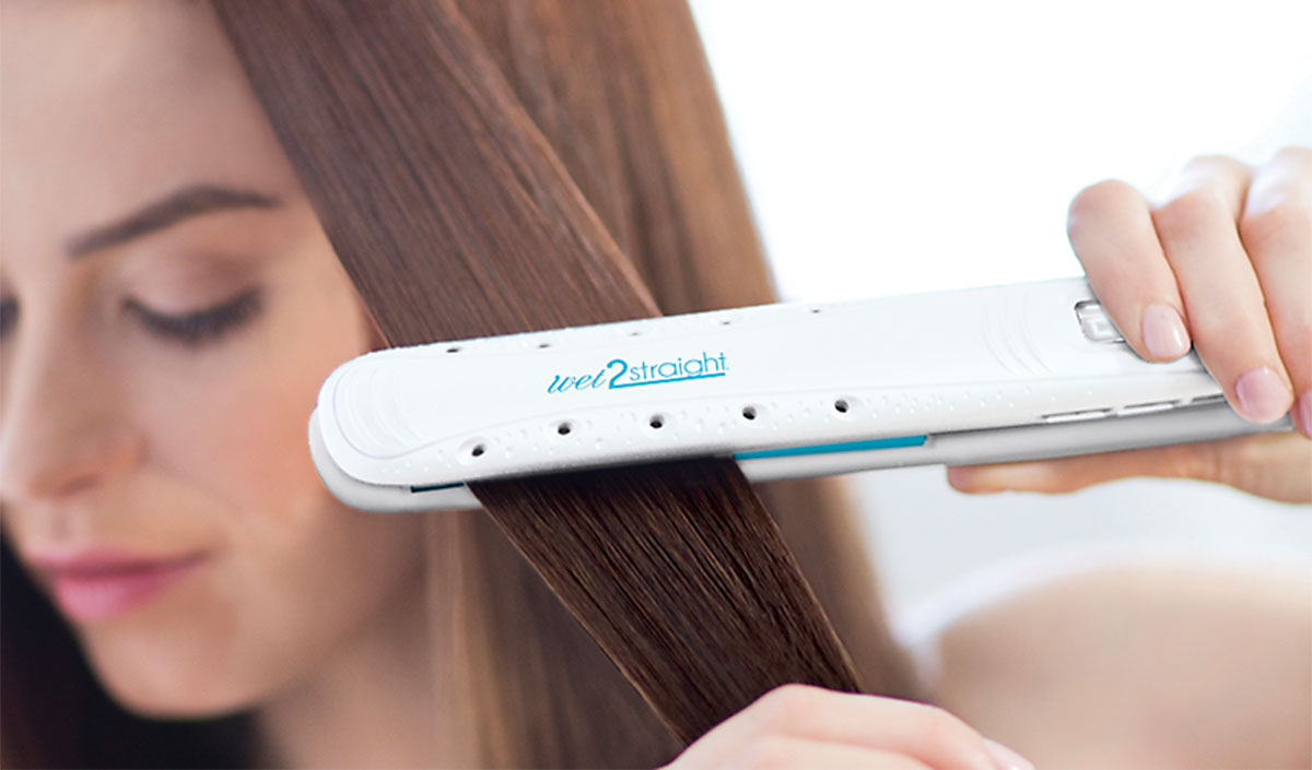 Mujer alisando cabello con plancha que seca el cabello a la vez