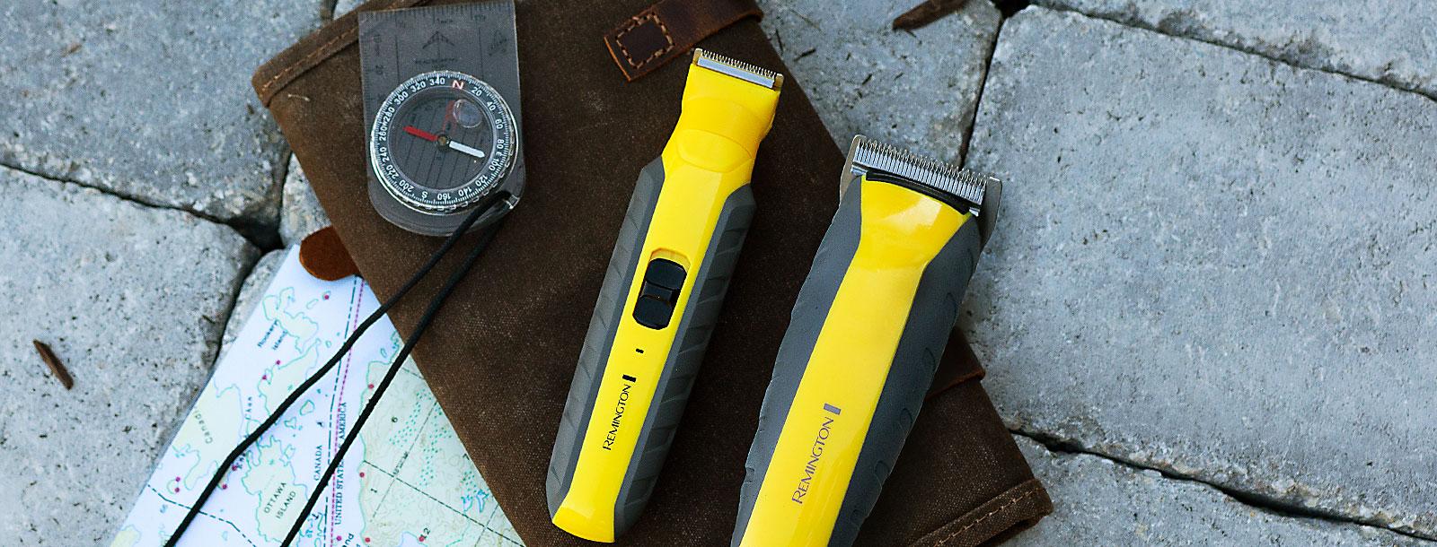 Dos máquinas de afeitar Remington Indestructible sobre bolsa de cuero, mapa y brújula.