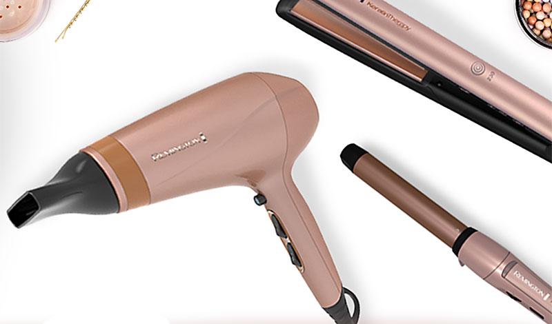 Secador, rizador y plancha alisadora de cabello de color marrón claro en fondo blanco.