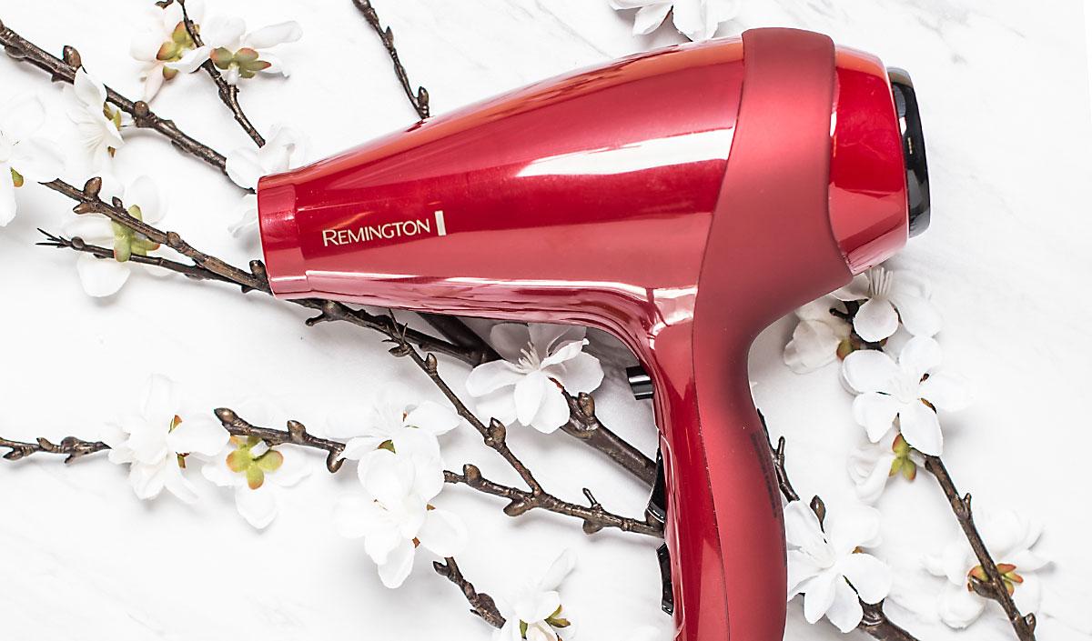 Secador profesional rojo apoyado sobre flores blancas