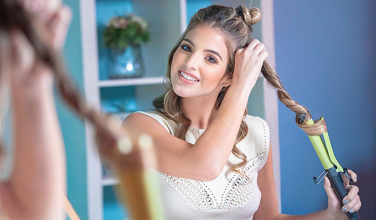 Mujer rizando su cabello con el rizador Remington Shine Therapy