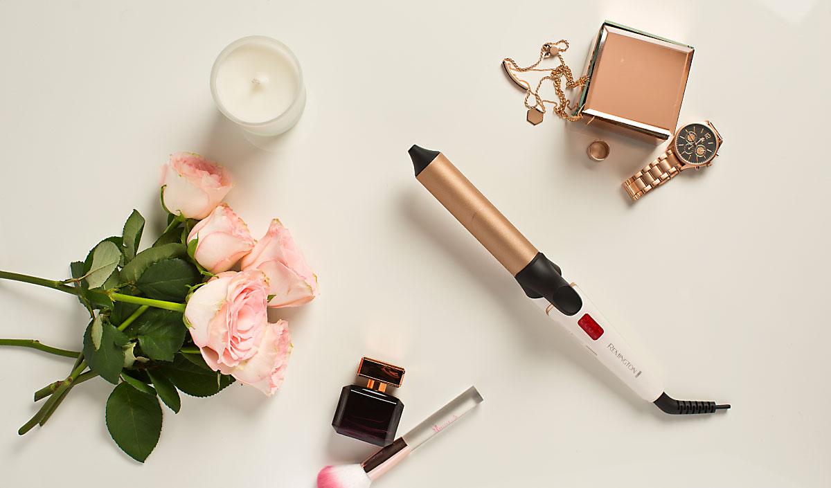Rizador de alto rendimiento en fondo blanco con rosas y complementos de moda