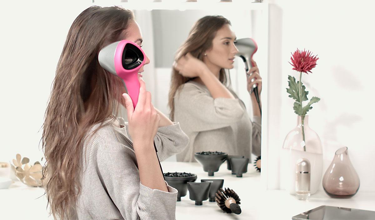 Mujer mirando su cabello brillante y ondulado frente al espejo