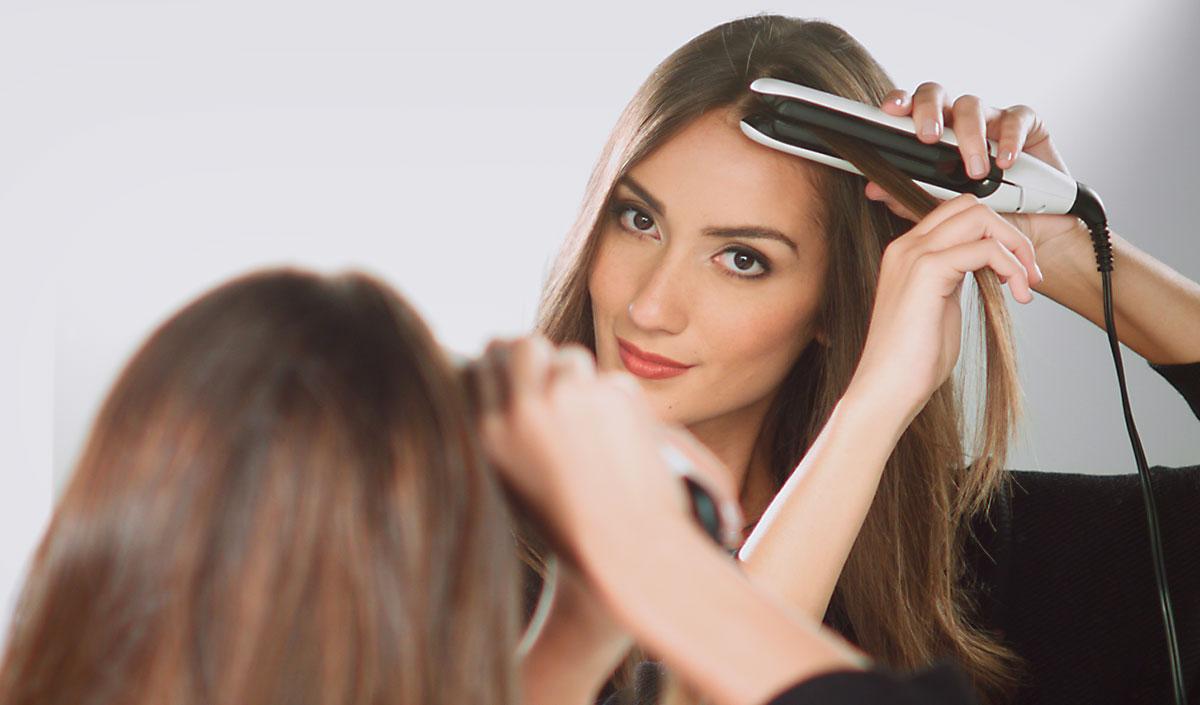 Mujer alisando su cabello con plancha de placas flotantes fácil de usar